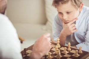 focused little boy playing chess together with father at home