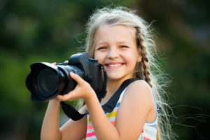 Portrait of cheerful smiling little girl holding photo camera in hands outdoors