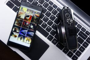 Photo of a smartphone,digital mirrorless camera and laptop computer