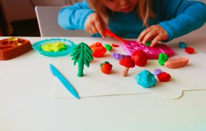 Child playing with clay molding shapes, preschool learning