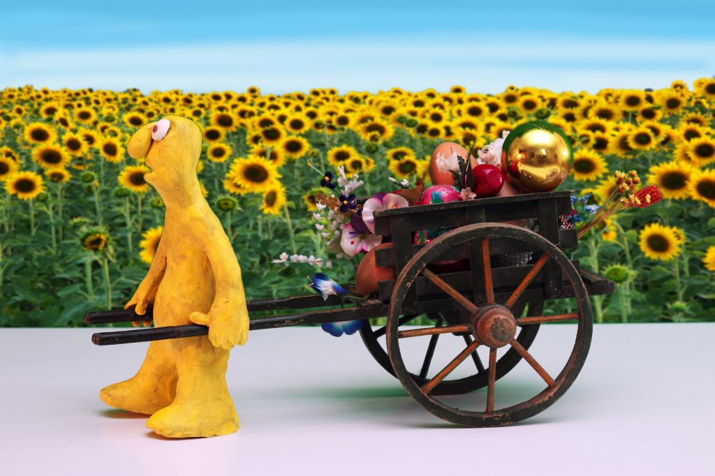 plasticine Character pulling hand-cart loaded with Spring Concepts